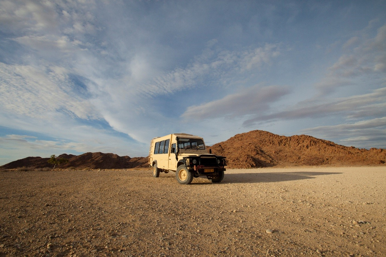 a land rover sitting in the immense desert of namibia