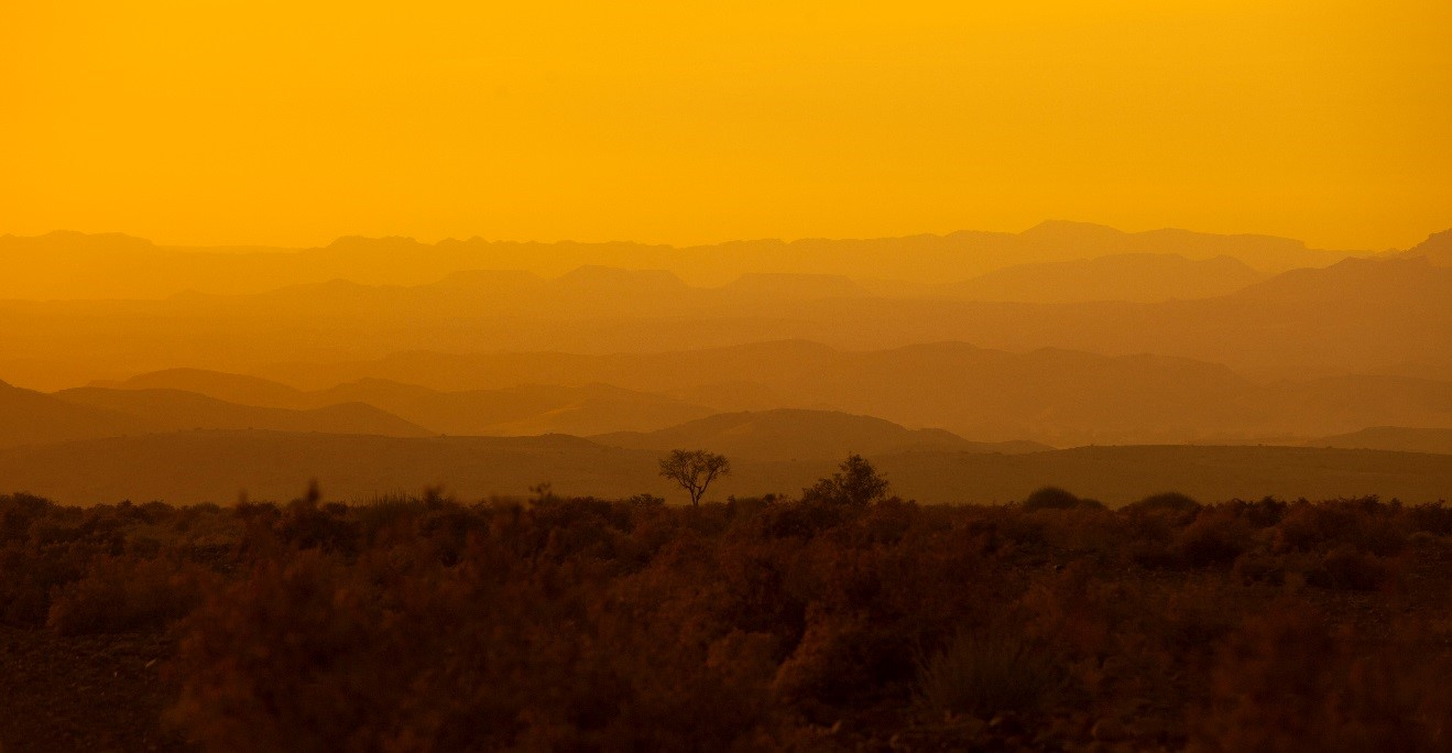 a glowing orange sunset with layers of hills in the background in namibia