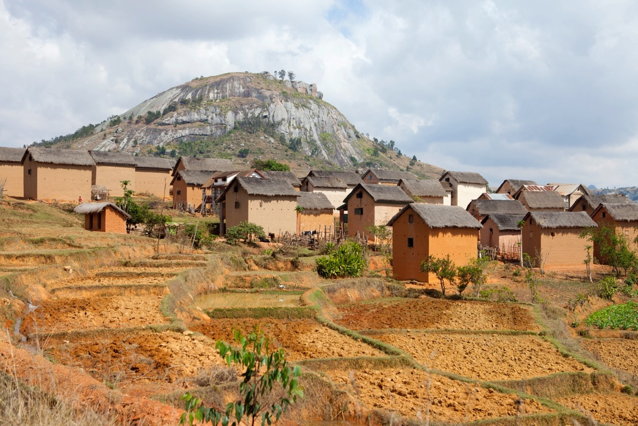 mud and clay houses built next to rice terraces in madagascar