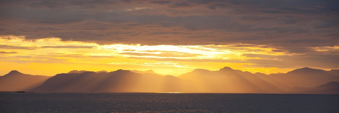 beautiful yellow sun rays coming down from the clouds in Glacier Bay, Alaska