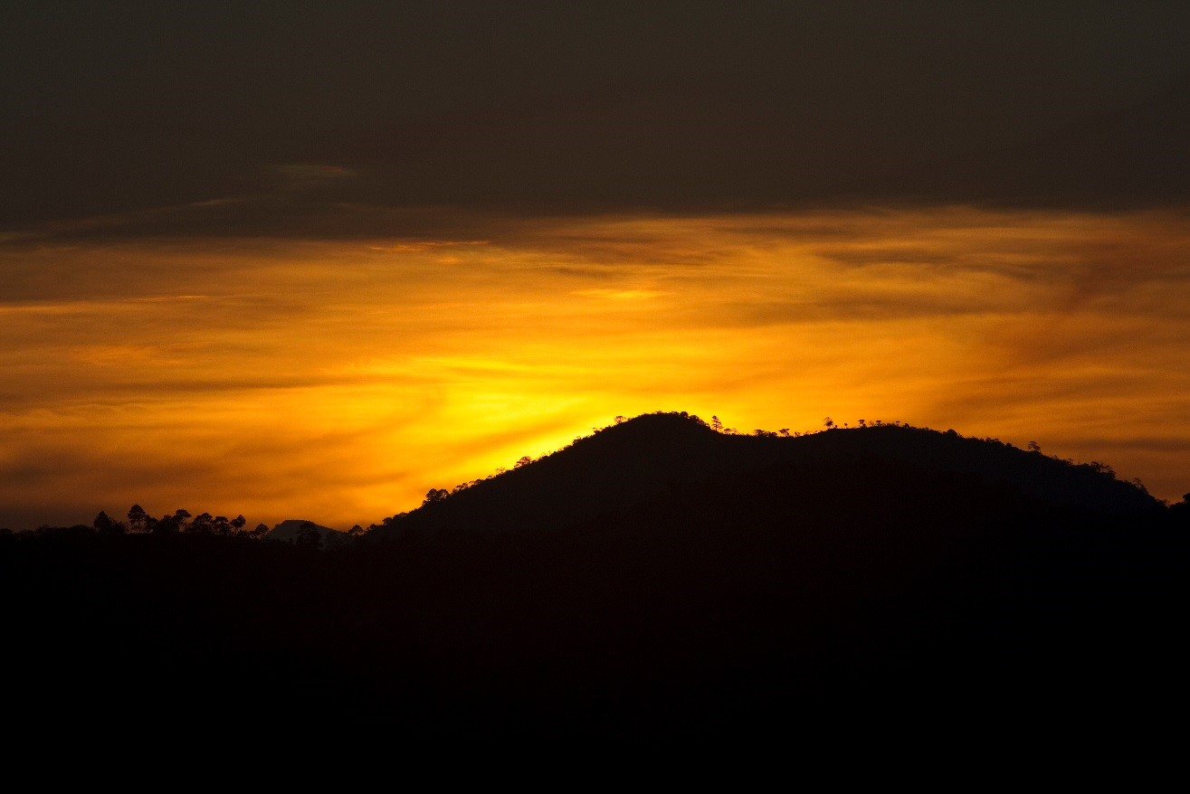 a zoomed in shot of an orange sunset before cropping it into a panoramic shot