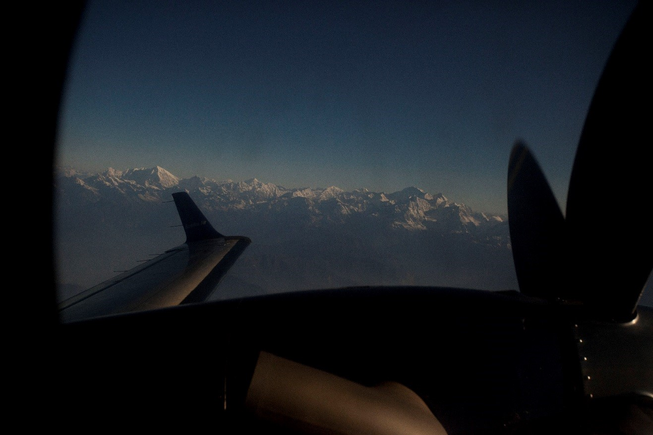 a view outside of the window while flying next to the himalayas
