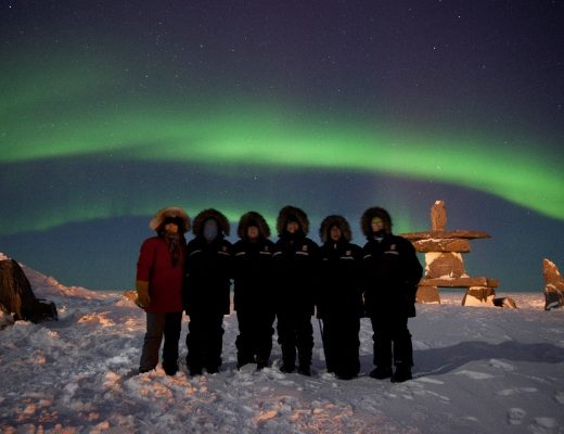 a group of travelers in front of the northern lights in Churchill Manitoba Canada