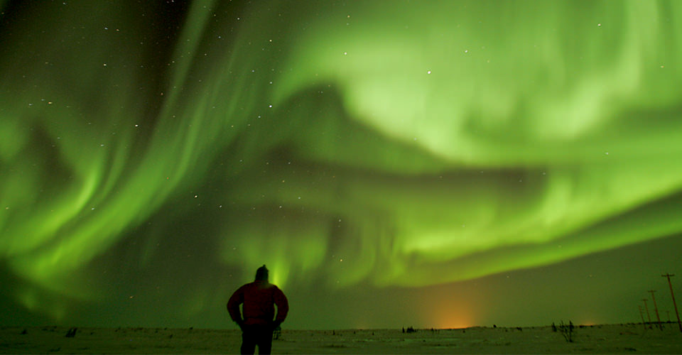 a single person is silhouetted in front of an incredible aurora display