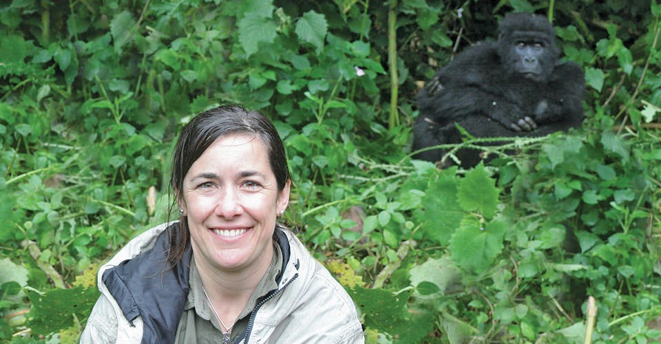 a woman sits in the brush with a large gorilla behind her