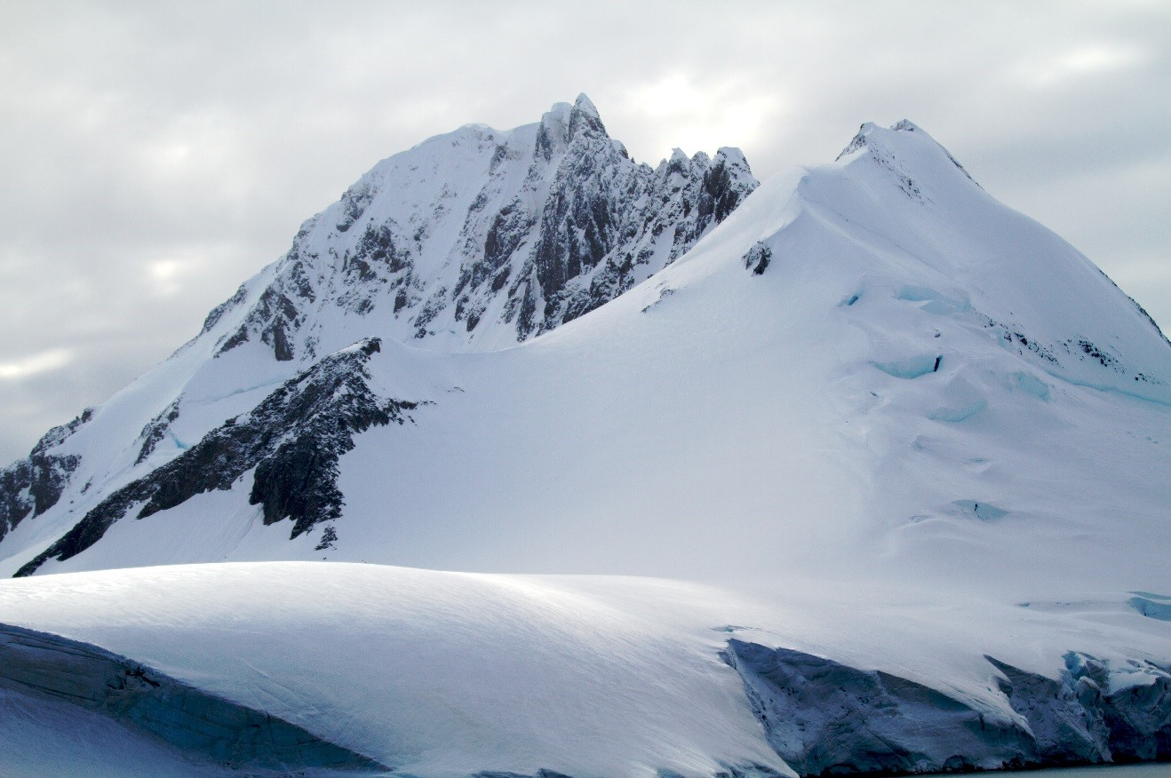 a large mountain in antarctic with a glacier in front of it