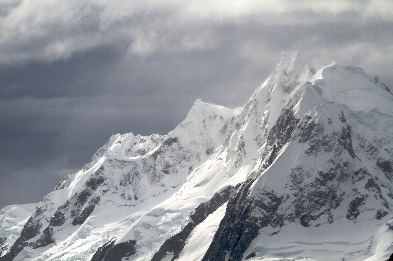 a jagged mountain range in antarctica amidst ominous storm clouds