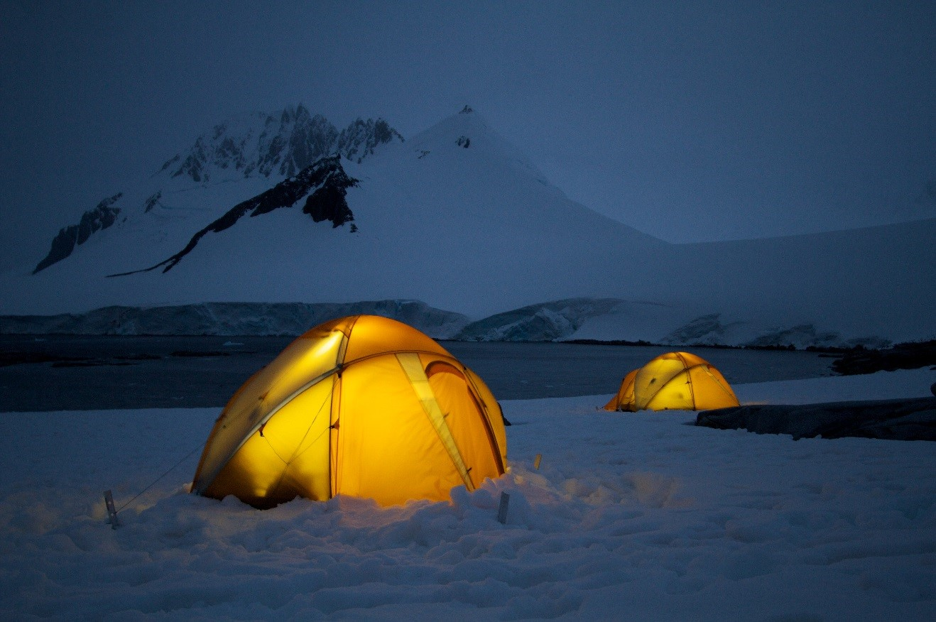 two glowing yellow tents photographed at the blue hour on the mainland of antarctica