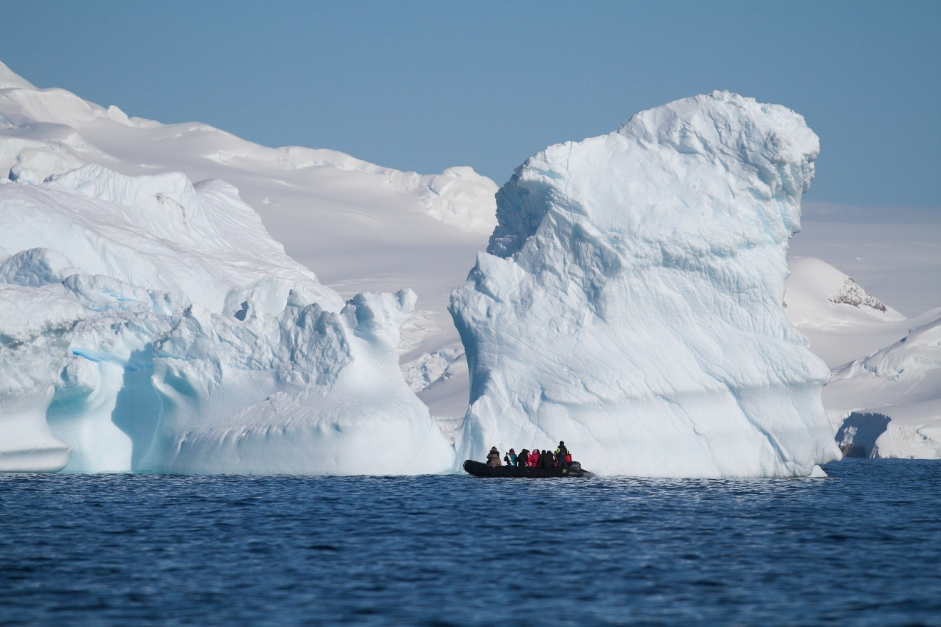 a zodiac floats along a large iceberg in Antarctica