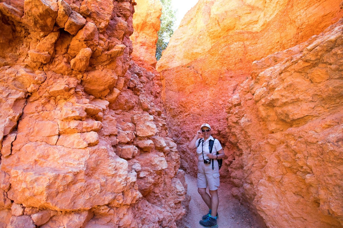 a colorful photo of a woman standing in a pathway with orange red and yellow rocks on either side