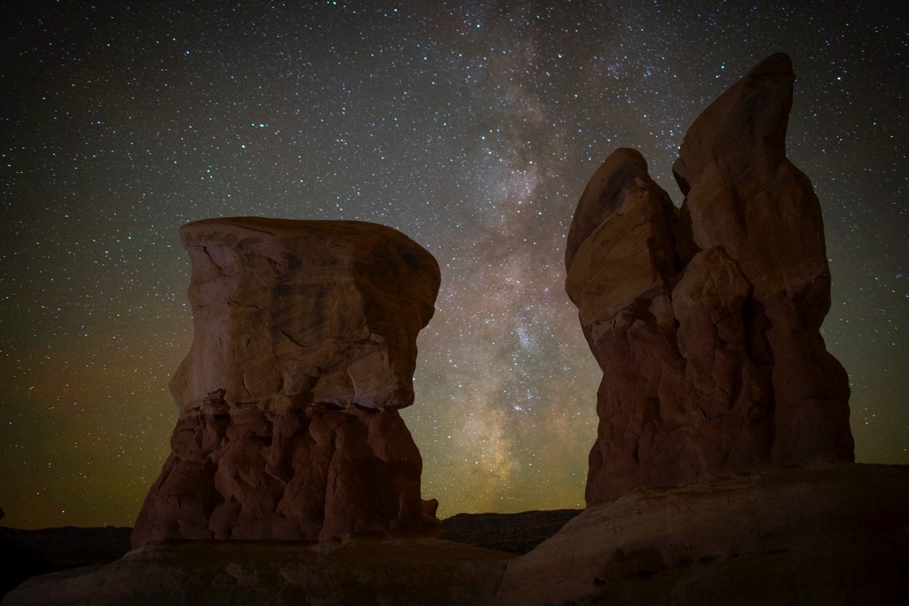 stone pillars frame an incredible view of the stars and milky way of Escalante National Monument