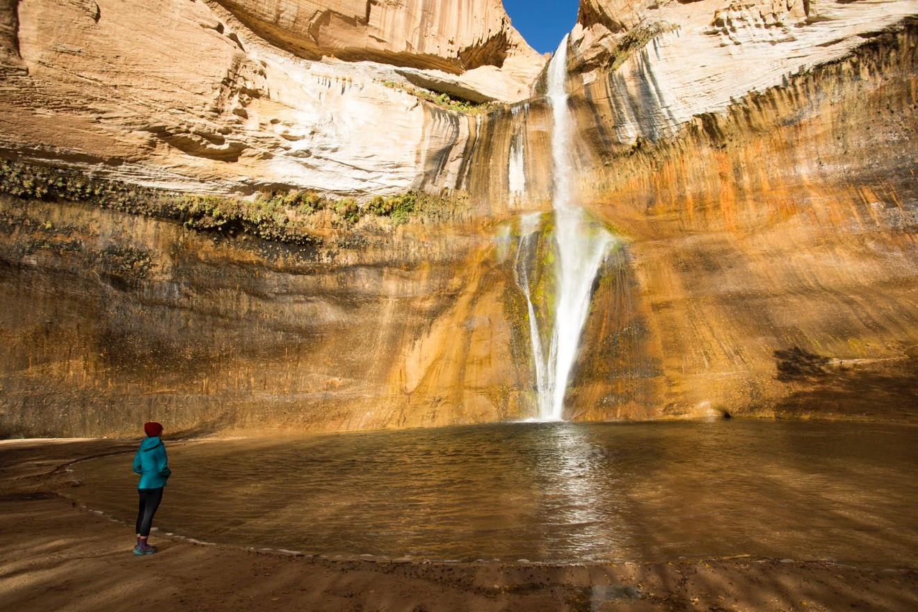 a woman peers at the majestic calf creek falls in Escalante National Monument
