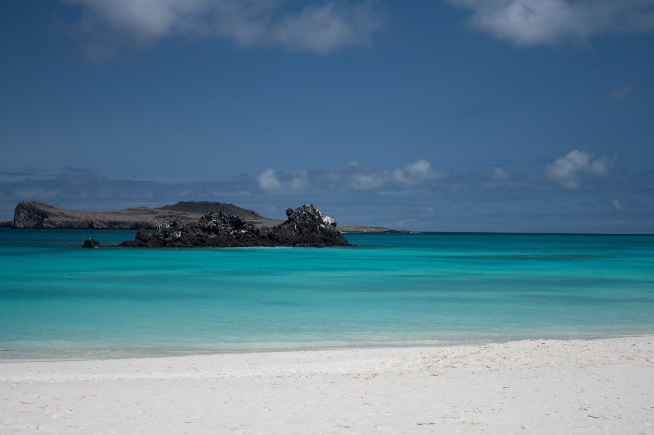 a beautiful photo of turquoise water and blue skies over gardner bay in Galapagos