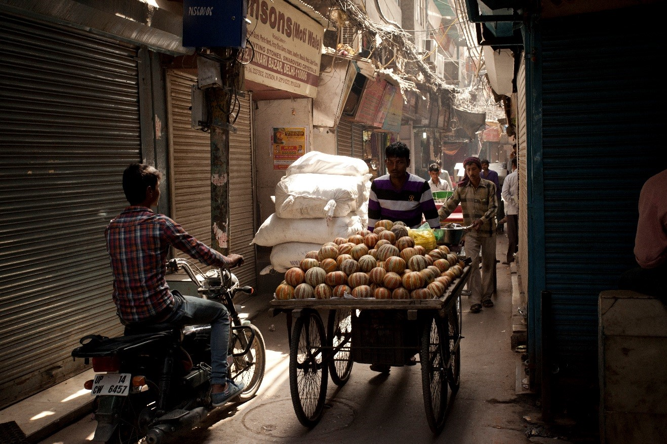 a dimly lit photo of the streets of new delhi with a vendor pushing a cart