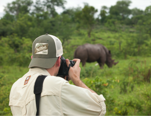 a photographer captures a photo of a rhino at close range while on foot in mosi oa tunya national park in Zambia