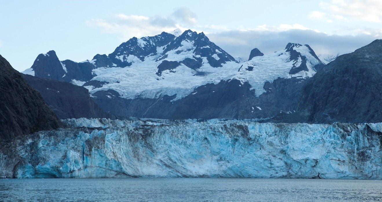 a stunning glacier with a towering mountain in the background in Glacier Bay, Alaska