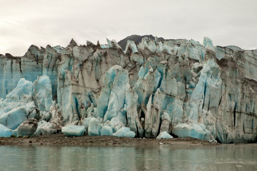 a jagged glacier comes closely to the water's edge in Alaska