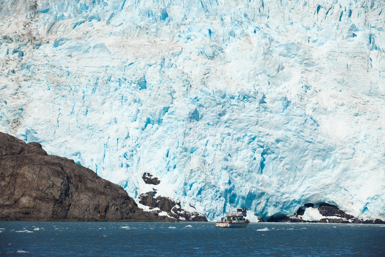 a massive glacier dwarfs a small boat in Kenai National Park, Alaska