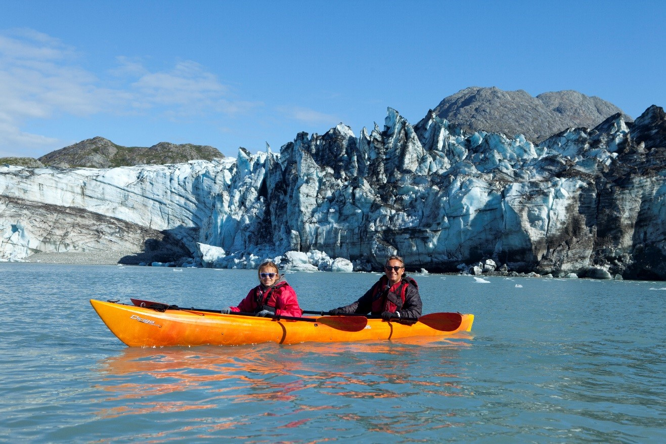 two kayakers sit in their boat in front of a glacier in Glacier Bay, Alaska