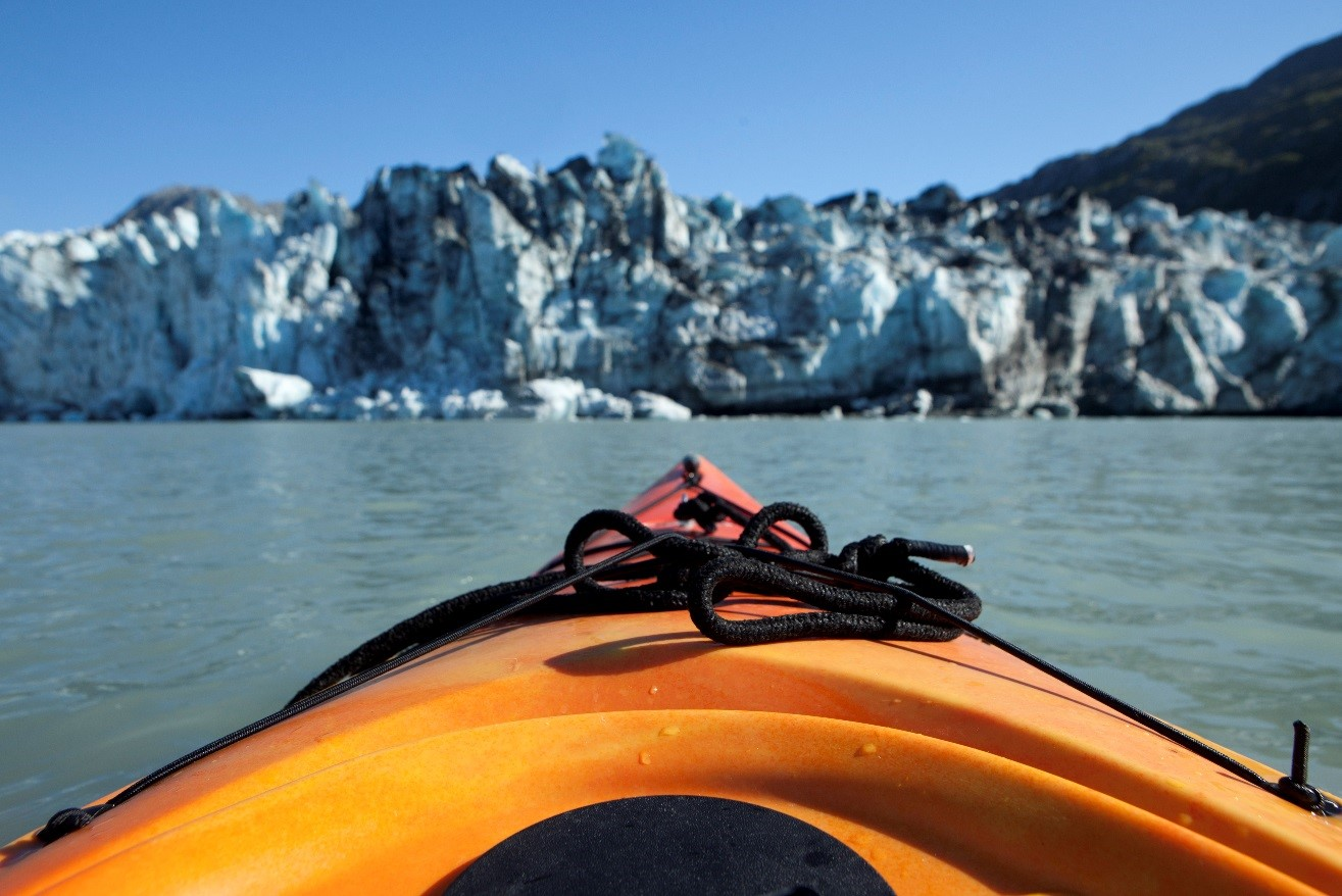 a kayak is pointed towards a glacier in an adventurous photo