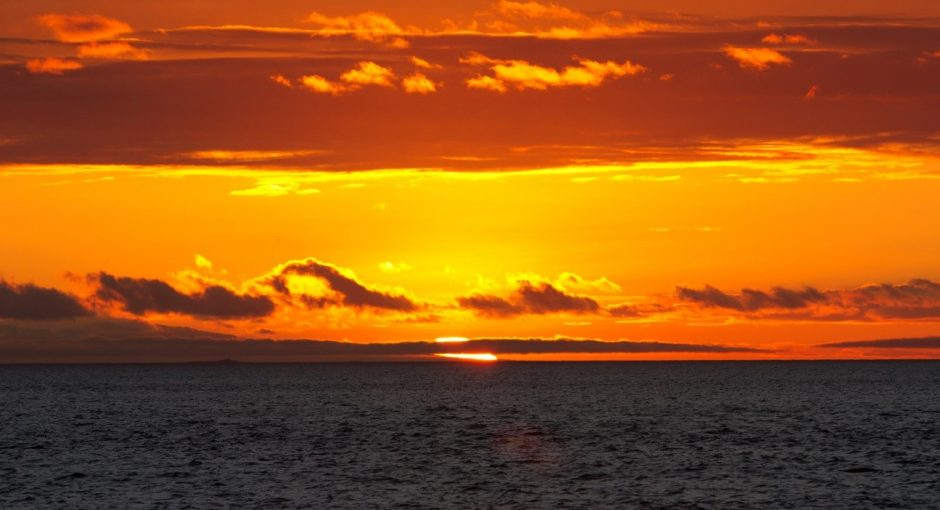 a bright orange and red sunset in the Galapagos over the horizon