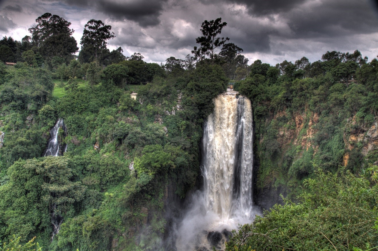 an ominous photo of a waterfall in kenya with storm clouds overhead