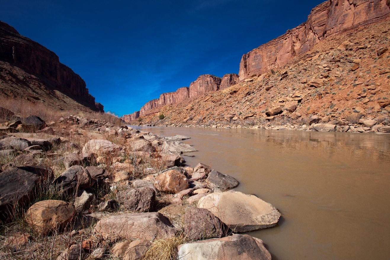 a crisp photo of blue sky above the mighty colorado river, flowing near Moab, Utah