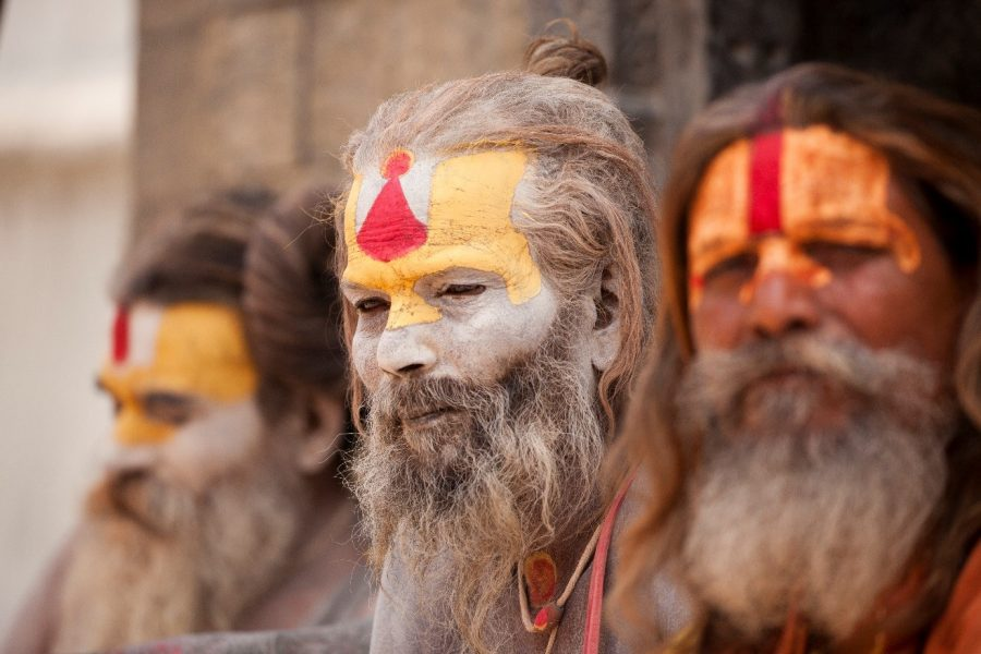 intriguing holi men with painted faces sit on the steps of a temple in kathmandu nepal
