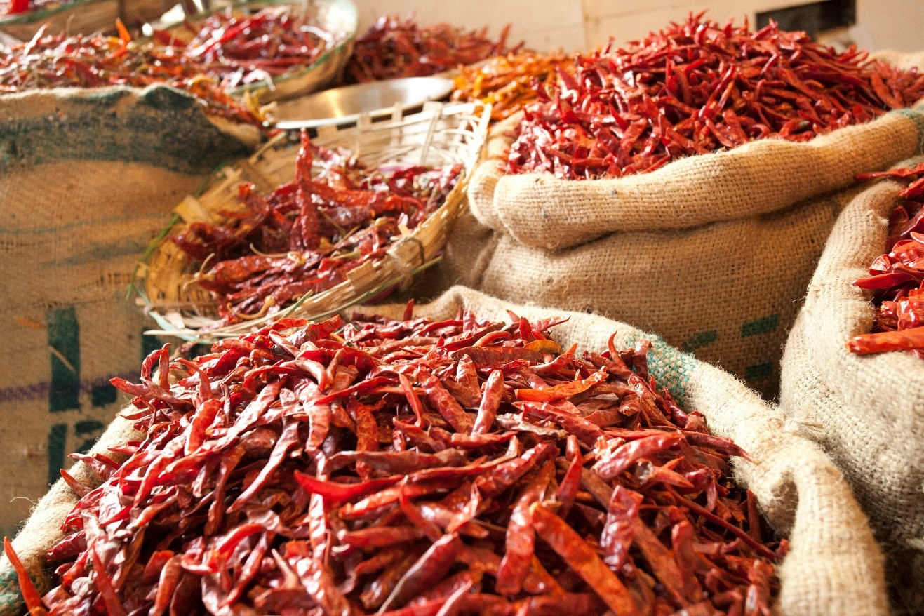 bushels of Chilis look fiery hot in a market in new delhi, india