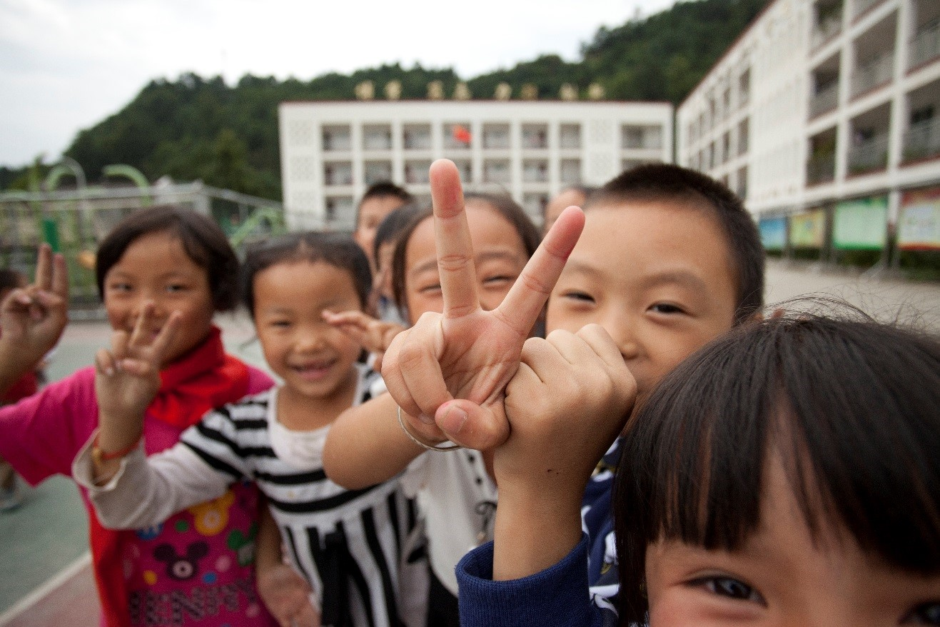 excited chinese children run up to me as a take a photo of them at their school