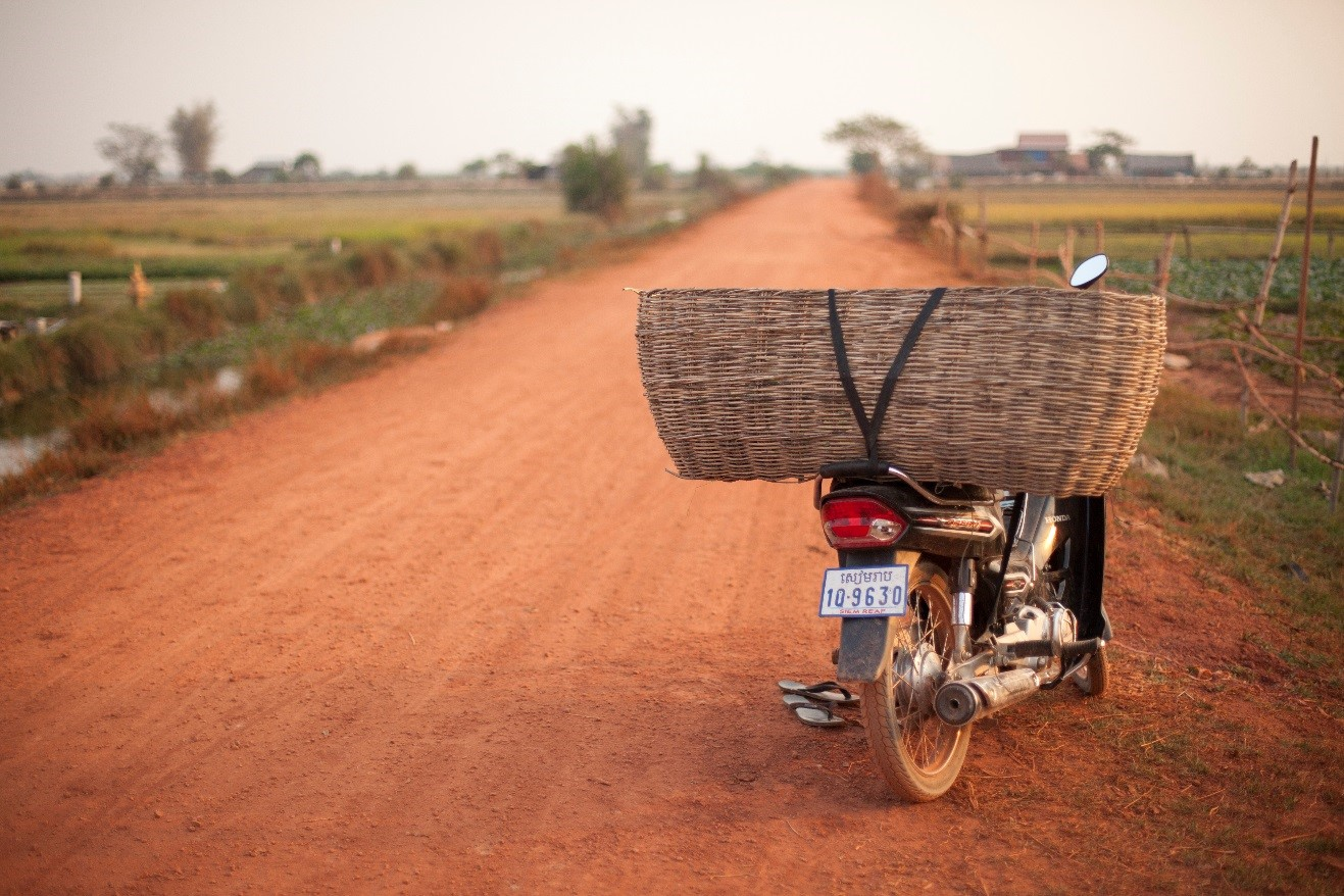 a motorbike with a basket sits on a dirt road in the countryside of cambodia