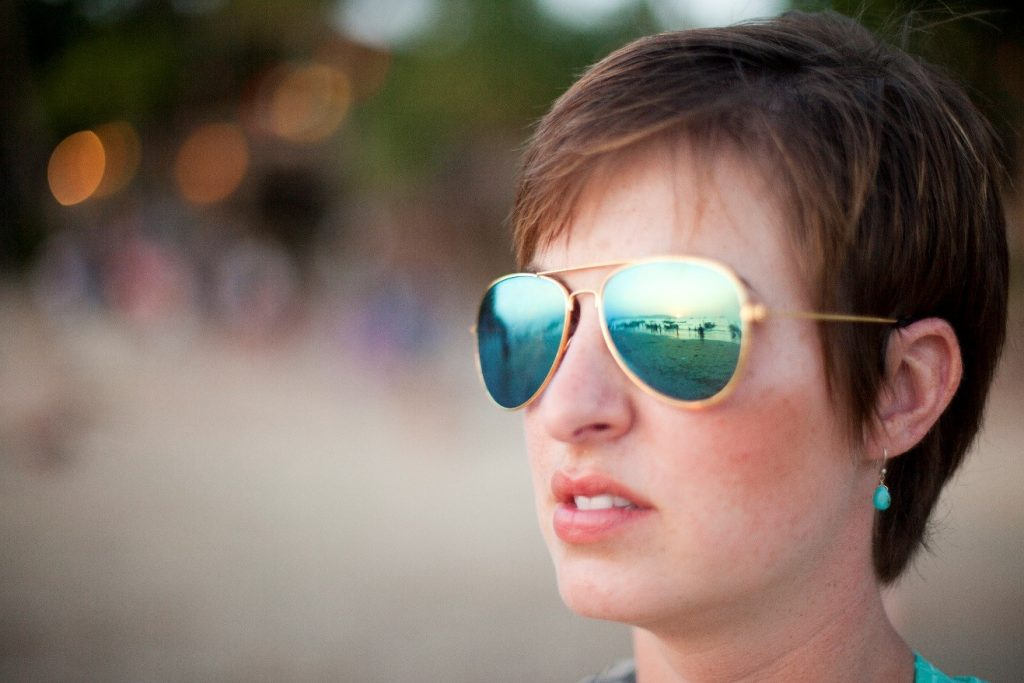 a portrait of a girl with reflections of boats in her sunglasses
