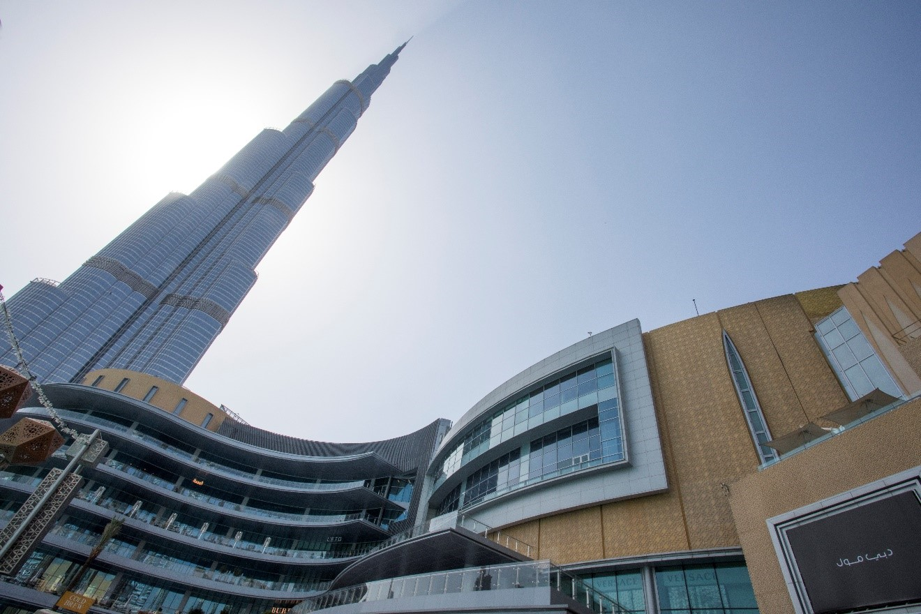 an outside, below view of the burj khalifa towering over the Dubai Mall