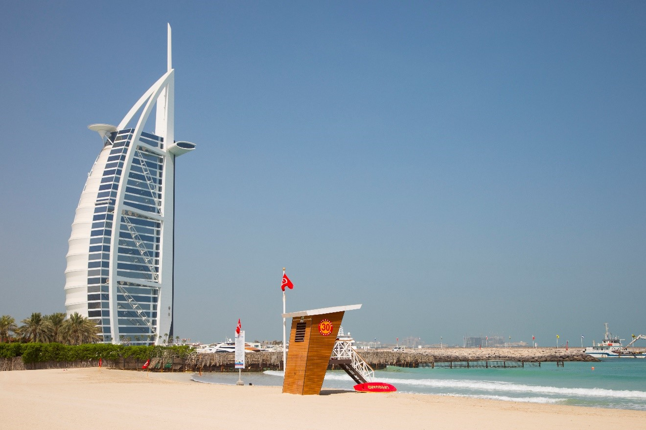 the burj al arab building situated on the shoreline of the persian gulf coast with lifeguard tower in front