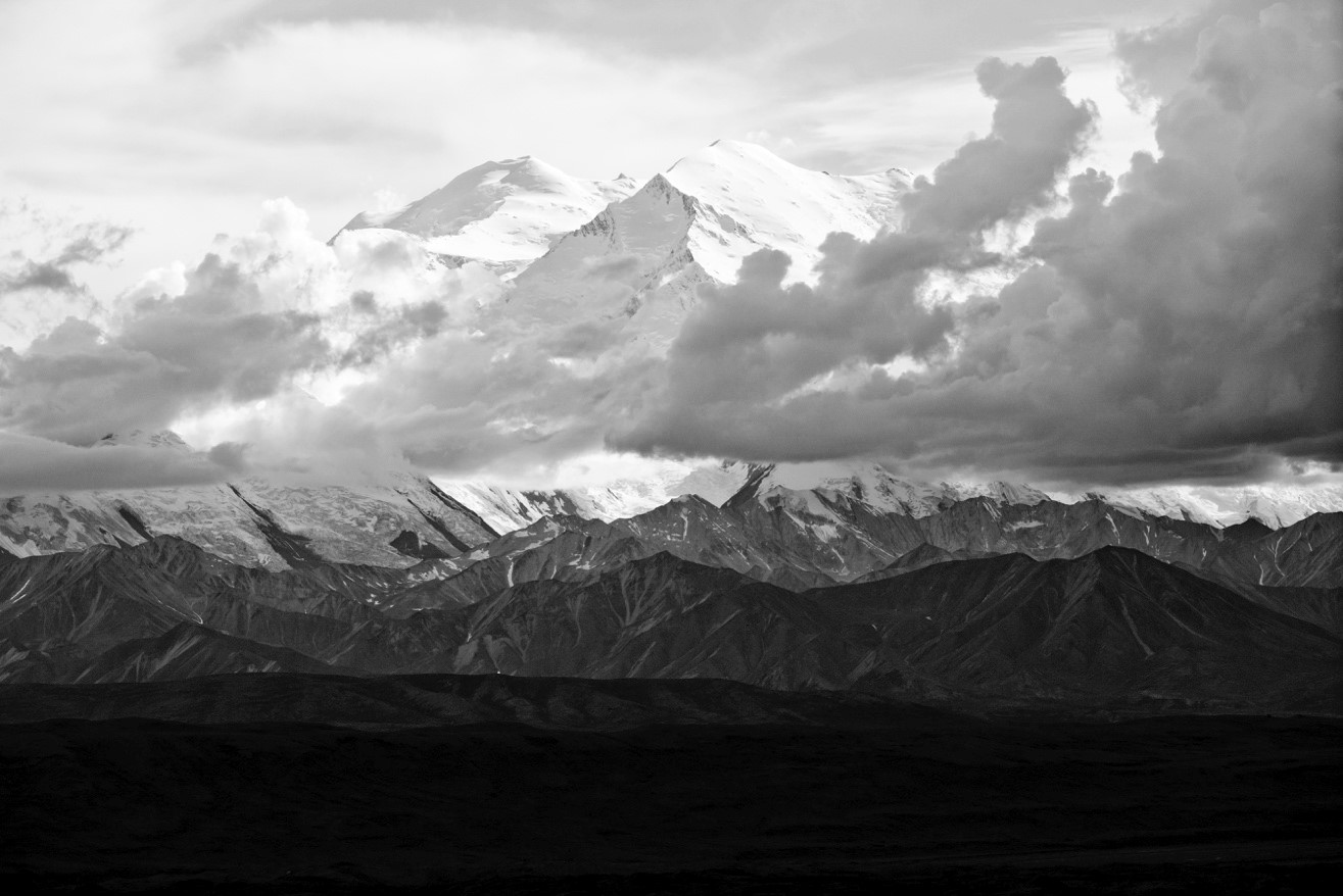 a black and white photograph of mount denali with clouds and ominous colors