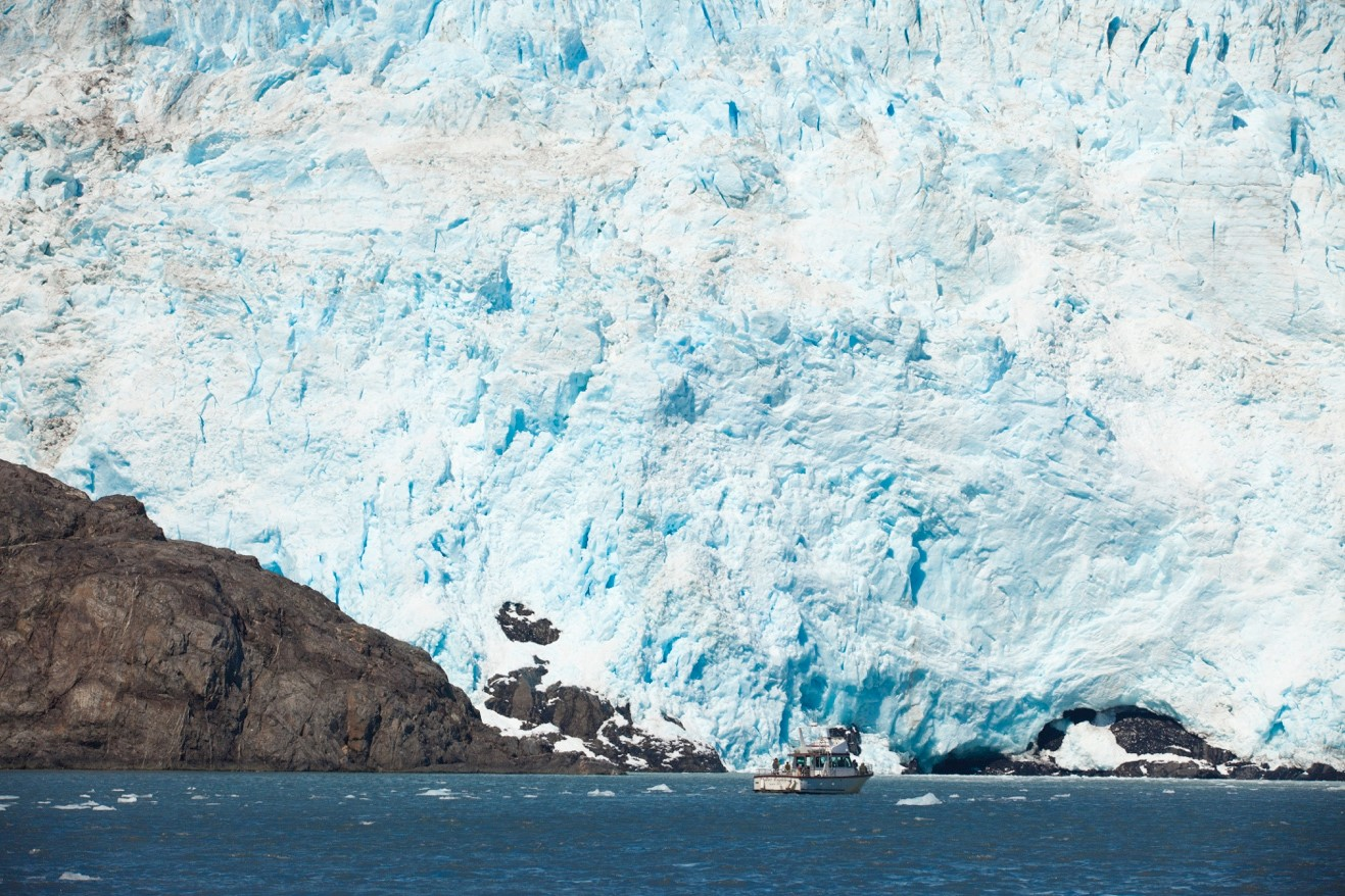 a photo of a towering glacier in kenai fjords national park with a small tour boat at the base of it