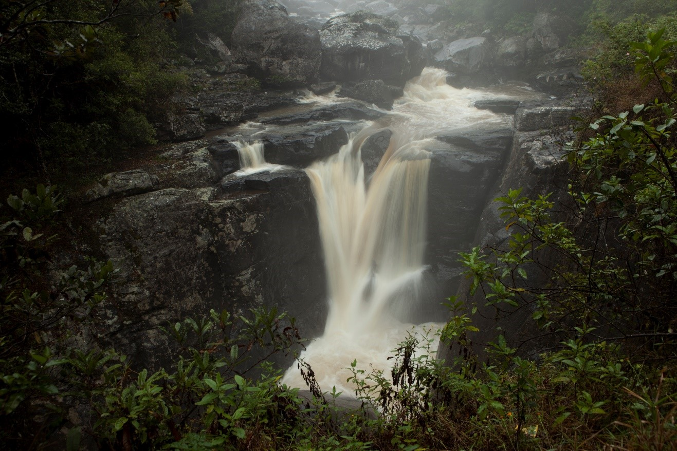 a waterfall pours down a slick rock face shrouded partially by mist in ranomafana national park, madagascar