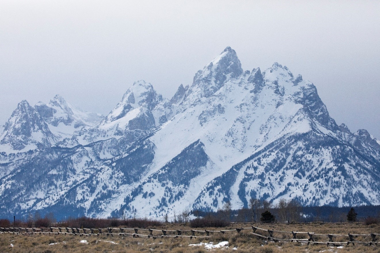 the grand teton sits mightily above the surrounding landscape