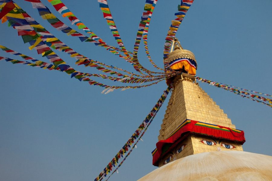 a stupa at a nepalese temple displays characteristic eyes and prayer flags