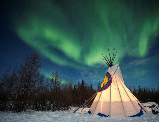 dramatic northern lights swirl over a metis teepee in Churchill Canada