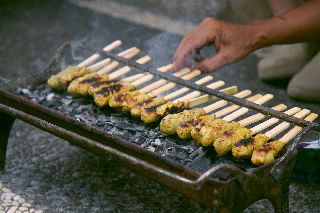 a shallow depth of field photo of chicken satay grills on a small grill