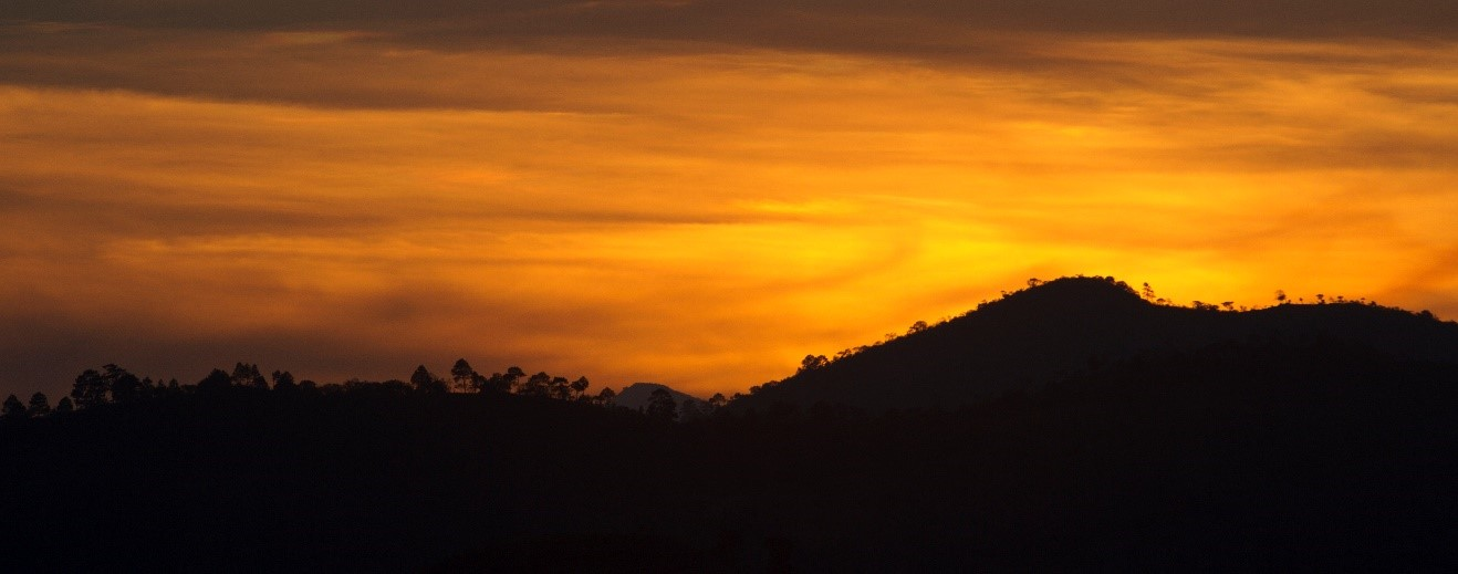 an orange sun sets below the mountains outside of Copan, Honduras