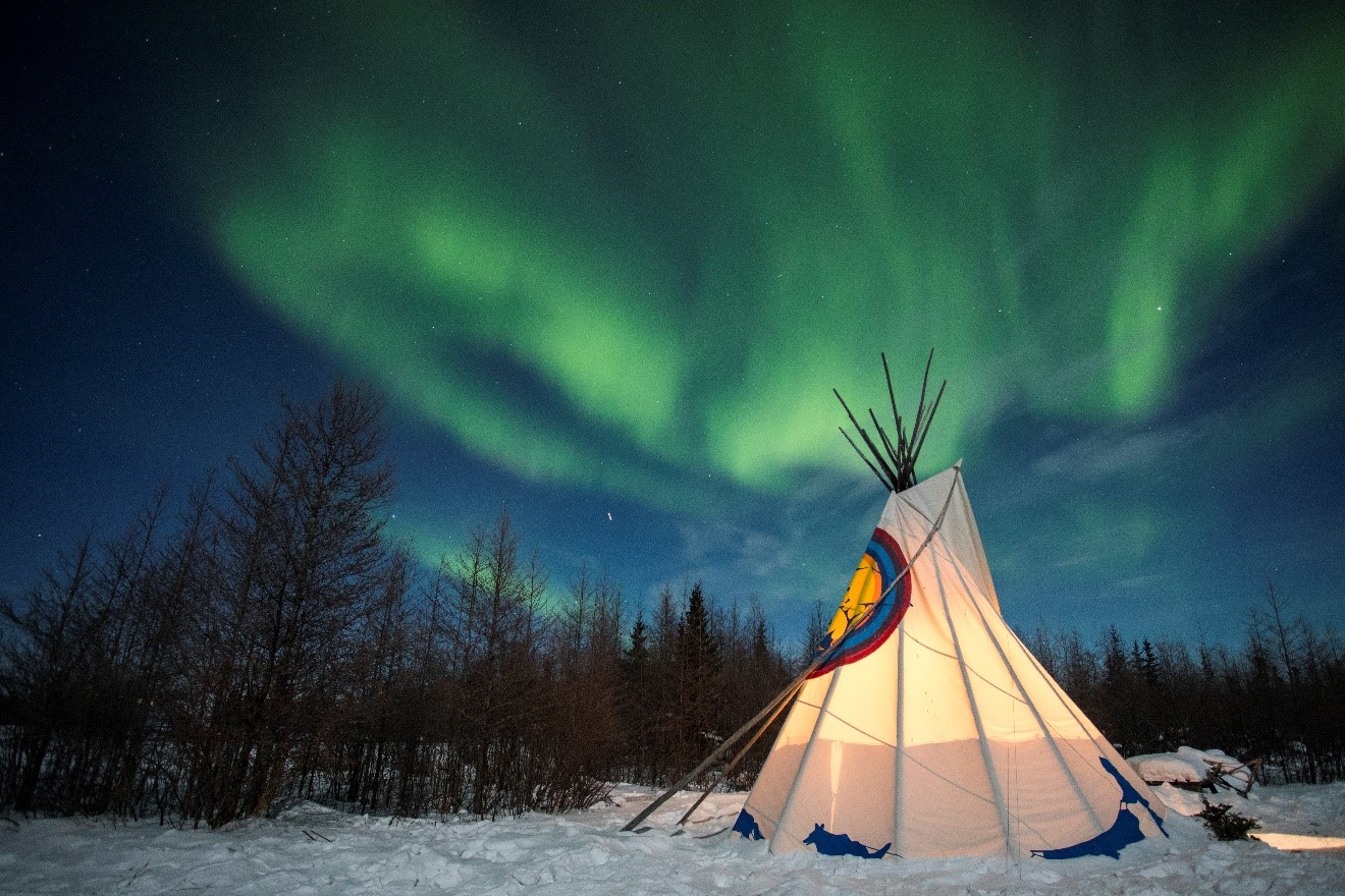 a lone tipee sits on the snow with northern lights overhead in the arctic