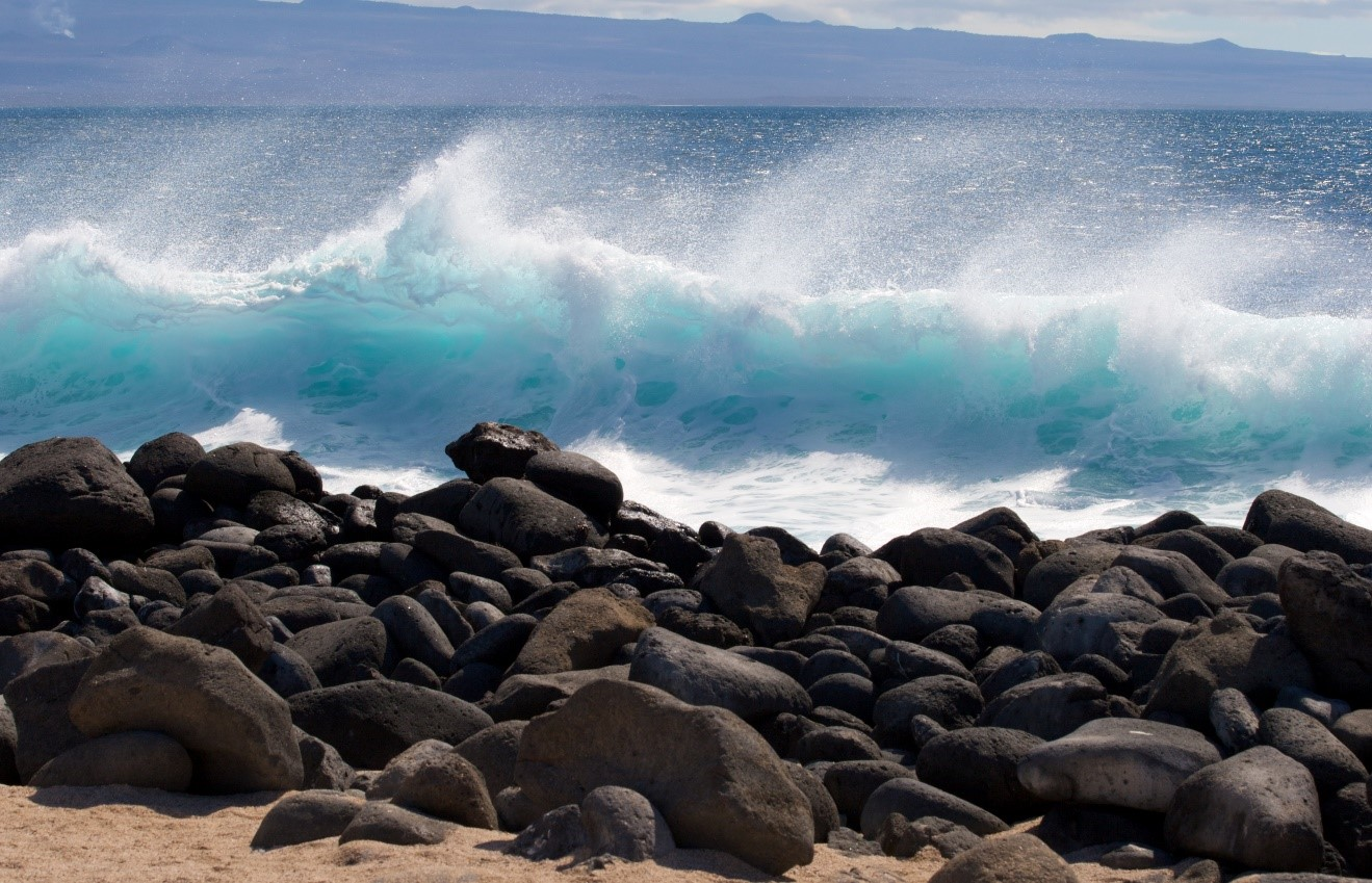 a blue wave crashes on the shore of the galapagos islands