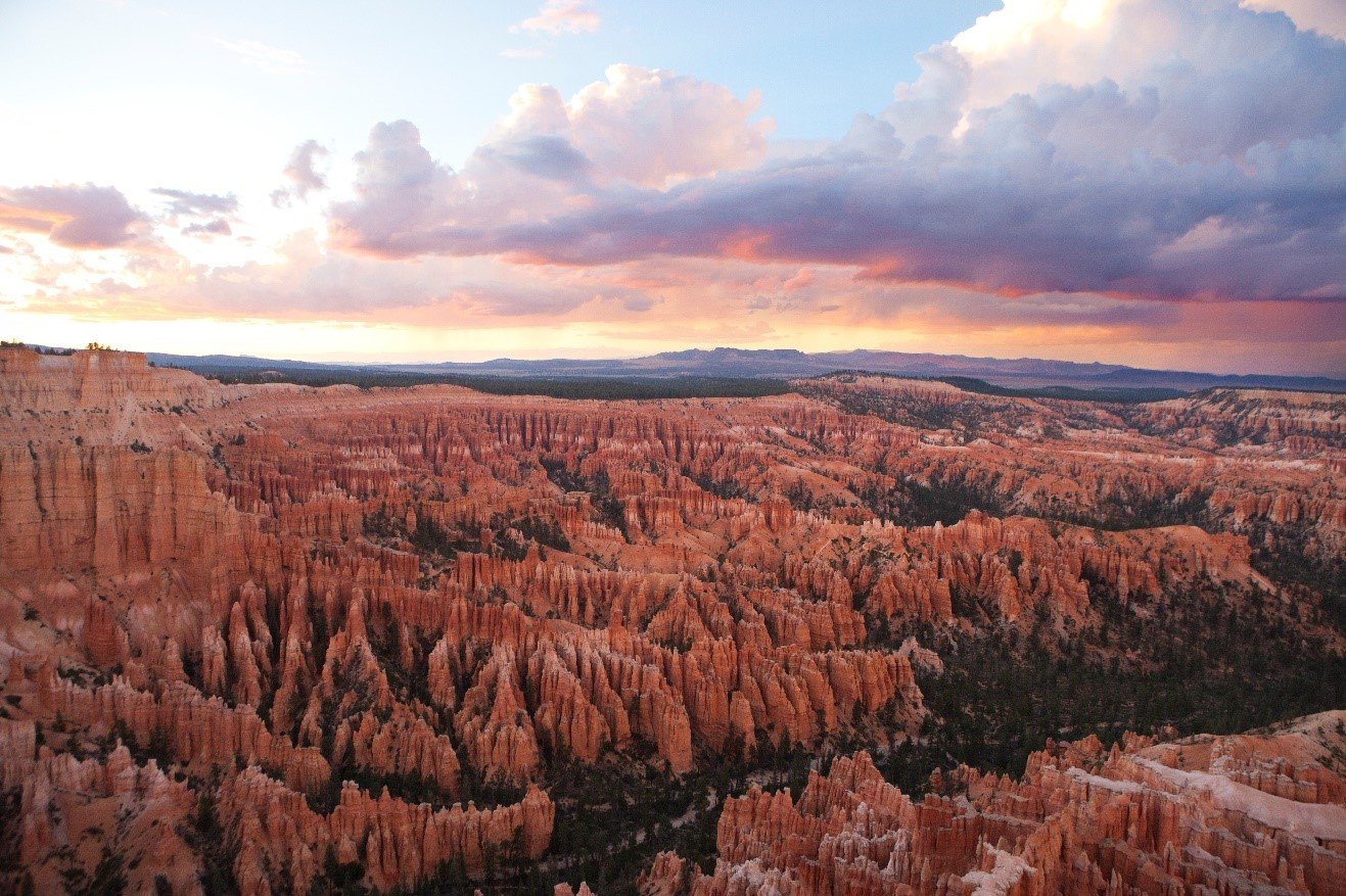 a colorful sunset emerges over the rim of bryce canyon national park