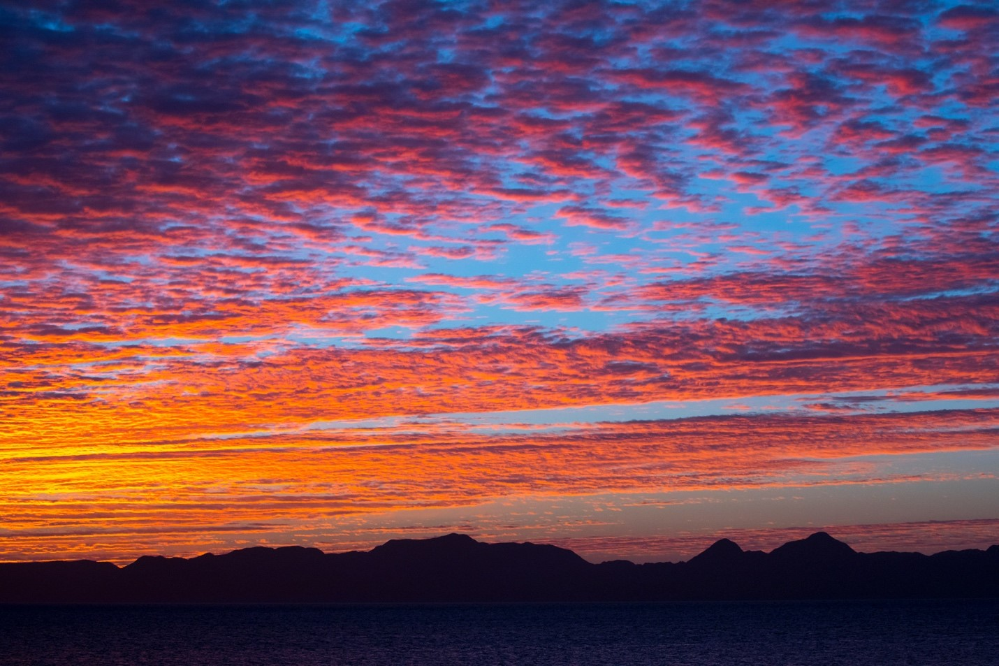 a sunset shimmers over the mountains in baja