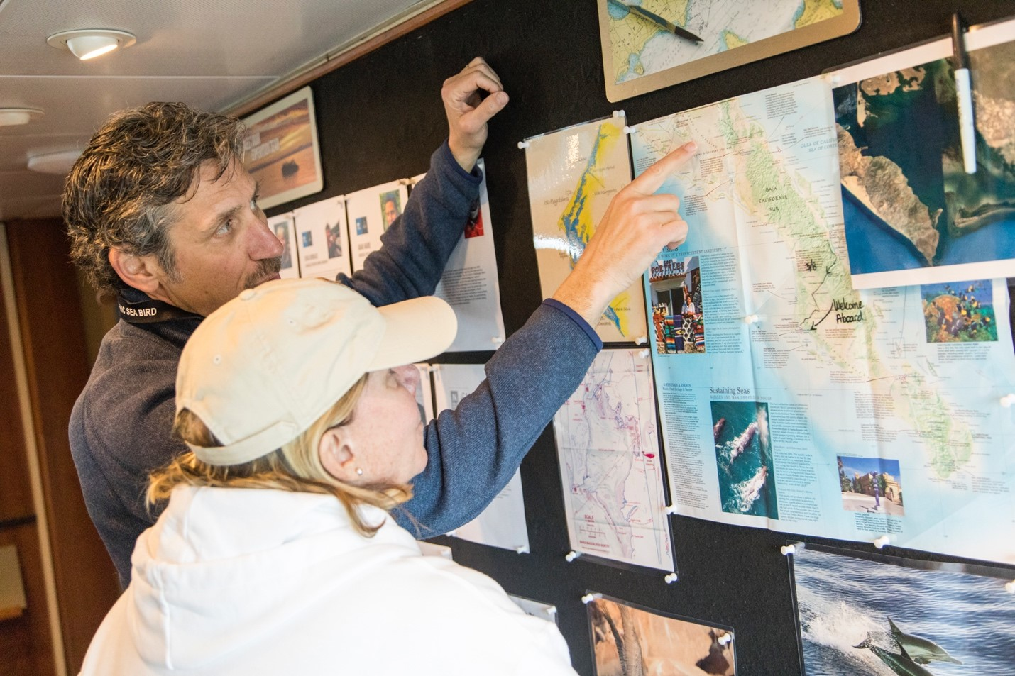 travelers looking at a map on board an expedition vessel in baja