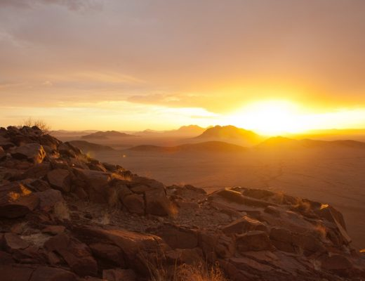 a spectacular sun set shines on the horizon of the namib desert