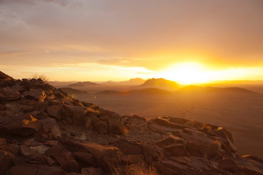 a spectacular sun set shines on the horizon of the namib desert