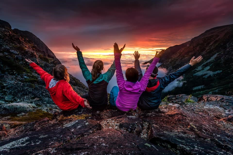four friends show exuberance as the sun sets in the distance